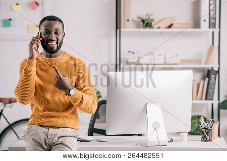 Smiling Handsome African American Designer In Orange Sweater Talking By Smartphone And Pointing On G
