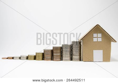 Close Up Growth Of Coins Stacking And Paper House On Isolated White Background For Financial Profit