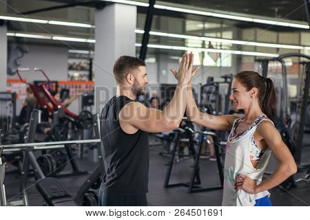 Fitness Man And Woman Giving Each Other A High Five After The Training Session In Gym