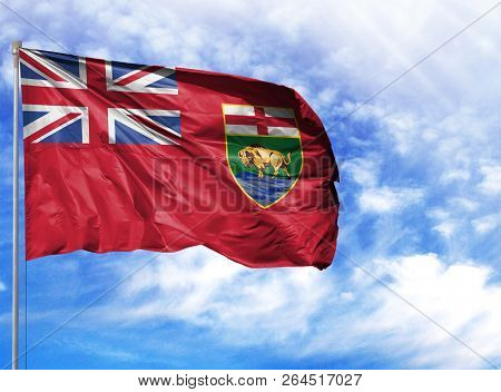 Flag Of Manitoba On Flagpole Against The Blue Sky