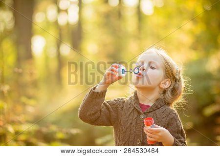 Portrait Of Funny Lovely Little Girl Blowing Soap Bubbles.cute Blonde Blue-eyed Girl In Yellow Knitt