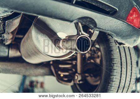 Car Emission Test Theme. Modern Compact Car Muffler Closeup.
