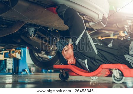 Caucasian Car Mechanic In His 30s Under The Car On The Mechanics Creeper Trying To Fix Modern Vehicl