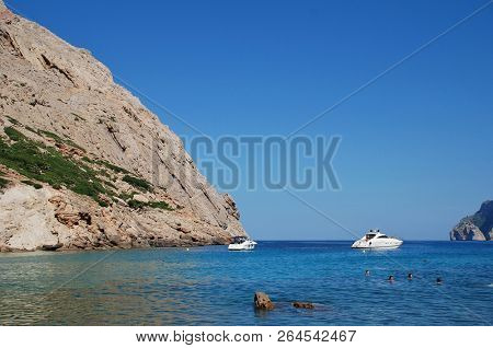 MAJORCA, SPAIN - SEPTEMBER 30, 2018: People swim in the Cala de Boquer on the Spanish island of Majorca. The cove lies at the end of the Boquer valley walk through the Tramuntana mountains.