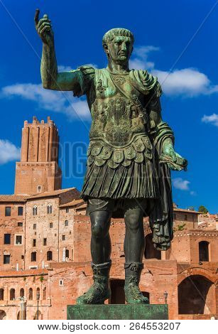 Caesar Augustus Trajan, Emperor Of Ancient Rome. Bronze Statue With Imperial Fora Ruins And Tower Of