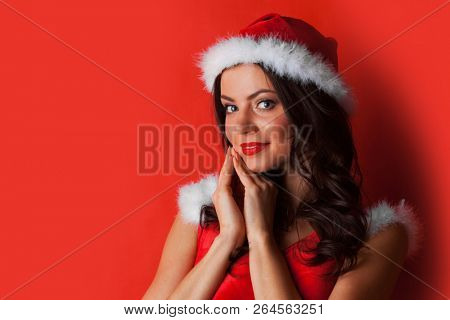 Pretty Pin-up style Santa girl in red hat and dress on red background