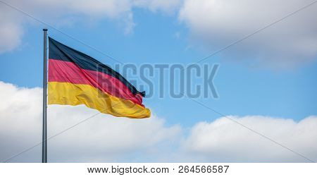 German flag waving on flagpole. Blue sky with few white clouds background, copyspace, banner.