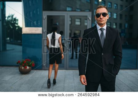 Serious bodyguard in suit and sunglasses, guarding poster