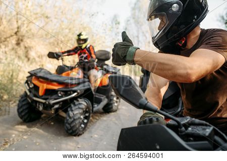 ATV rider showing thumbs up to his partner