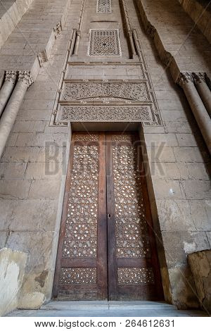External Old Decorated Bricks Stone Wall With Arabesque Decorated Wooden Door Framed By Stone Ornate