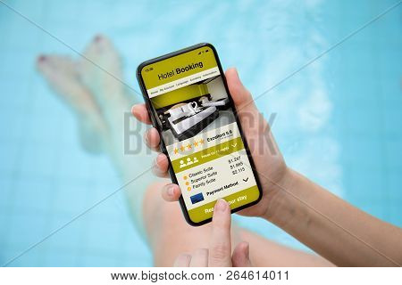 Woman In The Pool Holding Phone With App Hotel Booking On Screen