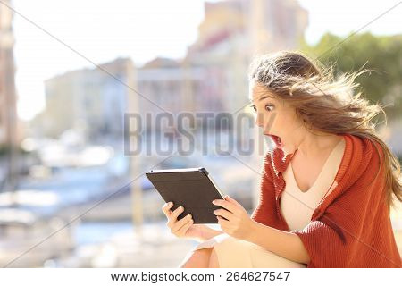 Shocked Woman Watching Online Content In A Tablet In A Coast Town