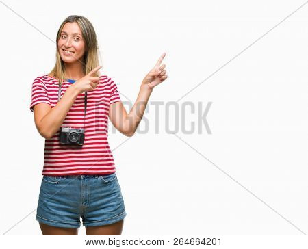 Young beautiful woman taking pictures using vintage photo camera over isolated background smiling and looking at the camera pointing with two hands and fingers to the side.