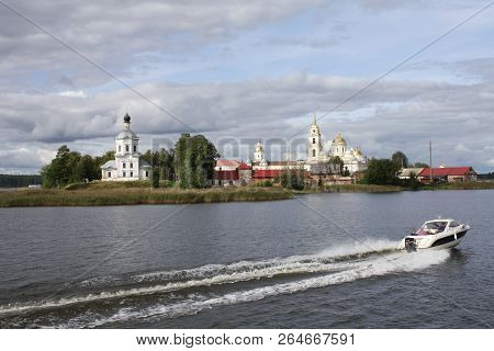 Motor Boat Sailing Past The Chirch Along The River, Nilov Monastery Seen From Water In Russia, Selig