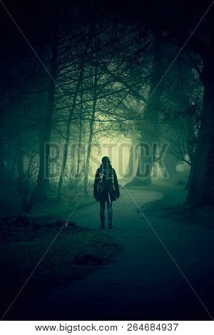 Woman walking on a path in a strange dark forest with fog - Halloween concept