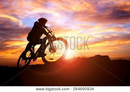 Mountain biker silhouette against the sunset concept for achievement, conquering adversity and  exercising