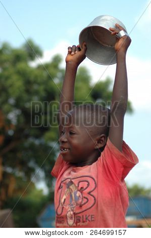 Donkorkrom, Ghana: July 20th 2016 - A Young Boy Holds A Bowl Used For Begging Above His Head Near Do