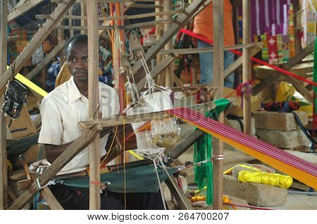 Kumasi, Ghana: 21st July 2016 - A Man Sits At A Loom In A Shop Making Traditional African Materials