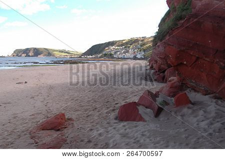 Red Coloured Sandstone Cliff And Rocks On Gardenstown Beach With The Village Visible In The Backgrou