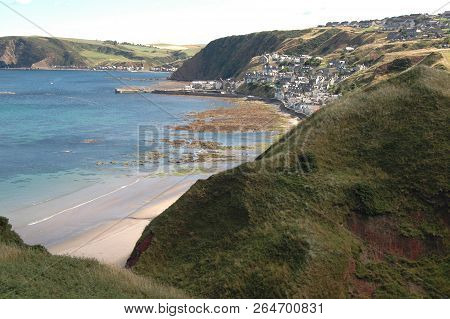 The Picturesque Village Of Gardenstown, Scotland, And Coastline Extending West.