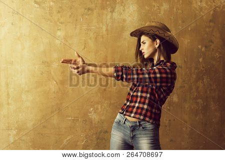 Cowboy Girl Or Pretty Woman With Blond, Long Hair In Stylish Hat And Red Plaid Shirt Showing Finger