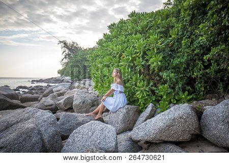 Pensive Young Woman With Long Hair Sitting On The Rock At The Tropical Sea Shore Near The Green Tree