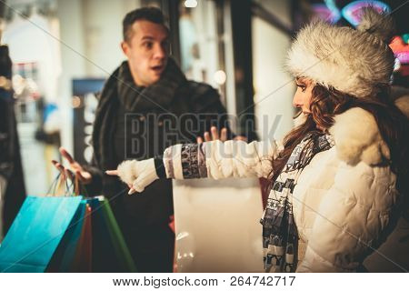 Young Beautiful Couple In The Shopping In The City Street At Christmas Time. Cute Girl Praying Her B