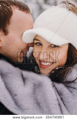 Stylish Couple In Love Hugging In Winter Snowy Mountains. Portraits Of Happy Romantic Man And Woman