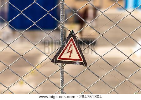 High Voltage Hazard Warning Sign On The Fence. Power Substation With Environmentally Friendly Electr