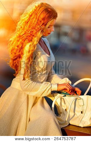 Fashion woman in autumn spring dress on city street. Female style of feminine fashionable girl model with long red wave hair and handbag on bench outdoor. Color tone on shiny sunlight background.