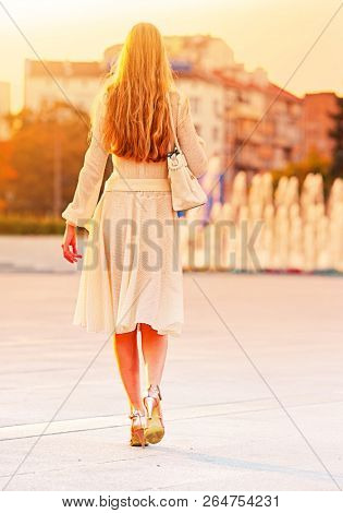 Fashion woman in autumn spring dress on city street and car. Back of female style of feminine fashionable girl model wallking hight heel fall outdoor. Color tone on shiny fountains sunlight background