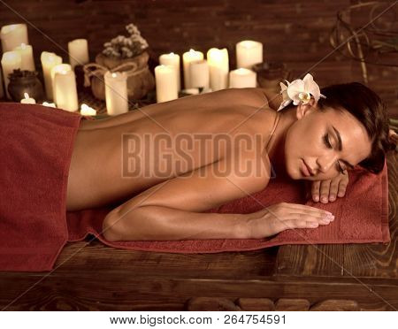 Chiropractic ayurveda massage therapy of woman in spa salon. Girl on candles background in massage spa salon. Luxary interior in oriental therapy salon. Brown sepia on dark .