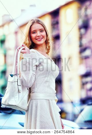 Fashion woman in autumn spring dress with flared skirt on city street. Female style feminine fashionable girl model with outdoor. Color tone car and building on shiny sunlight background.