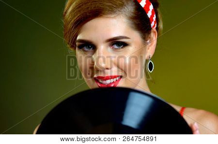 Dj retro woman vintage vinyl record . Pin-up retro female style portrait. Girl pin-up style wearing red dress. Retro style is one of most relevant on gradation brown background.
