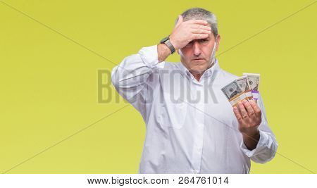 Handsome senior man holding bunch of money over isolated background stressed with hand on head, shocked with shame and surprise face, angry and frustrated. Fear and upset for mistake.