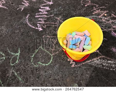 Yellow Bucket Of Chalk On Street Filled With Words And Symbols Drawn With The Sidewalk Chalk
