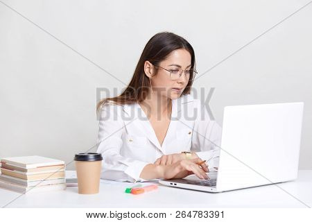Young Female Administrative Works On Laptop Computer, Searches Information In Internet, Dressed In W