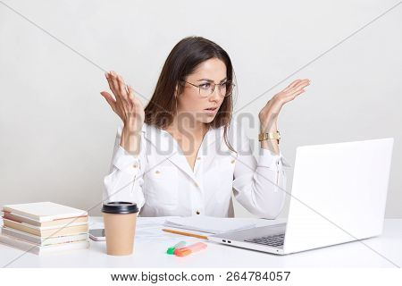 Puzzled Emotive Woman Has Deadline Task, Gesture With Frustration, Stares With Bugged Eyes, Wears Ro