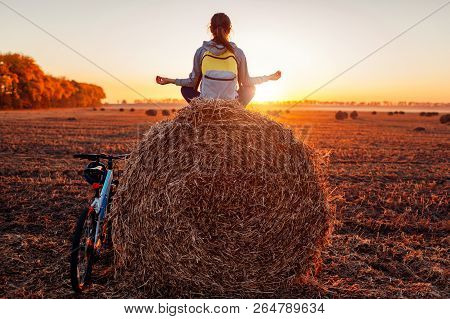 Young bicyclist meditates sitting on haystack after a ride. Woman having rest practicing yoga in autumn field. poster
