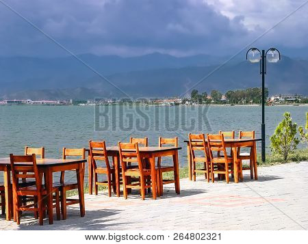 Cafe Tables On The Coast In Turkey. Cafe Tables On The Background Of The Sea, Mountains And Clouds