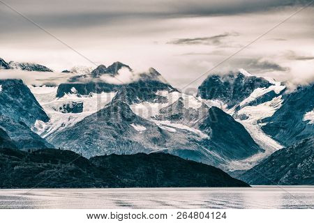 Glacier Bay National Park, Alaska, USA. Alaska scenic cruise travel view of snow capped mountains at sunset. Beautiful snowy mountain peaks landscape view from cruise ship vacations.