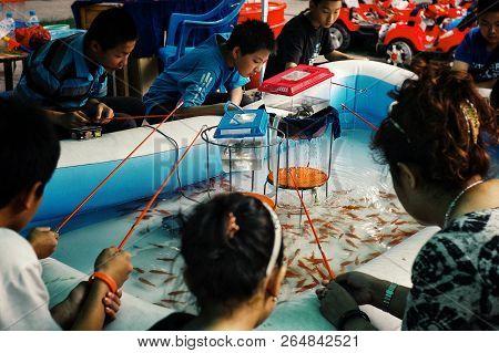 Urumqi / China - May 24 2011 : Young Boys And Girls Fishing Gold Fish From A Small Swimming Pool