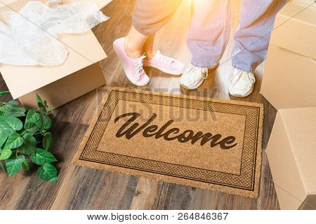Man and Woman Standing Near Welcome Mat, Moving Boxes and Plant.