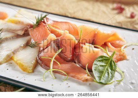 Exquisite Serving Restaurant Plate of Smoked Salted Raw White Fish Fillet with Red Fish Sashimi. Delicacy Fresh Seafood Dish with Toothfish, Salmon and Tuna Meat on Rustic Background Close Up poster