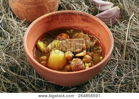 Homemade Lamb Soup Piti or Putuk with Cherry Plums in Vintage Ceramic Bowl on Rustic Background. Azerbaijani Bozbash with Mutton, Vegetables and Spices or Clear Sturdy Seasoned Broth Close Up poster