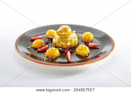 Fruit Dessert with Strawberries and Mango Sphere Isolated on White Background. Exquisite Serving Dish of Golden Ducky Cake with Apricots, Grapes and Berries on Elegant Restaurant Black Plate Close Up