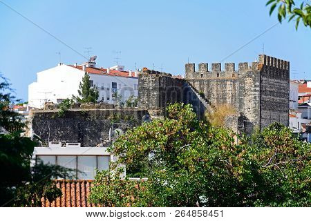 Tavira, Portugal - June 12, 2017 - View Of Part Of The Castle Battlements With Town Buildings To The