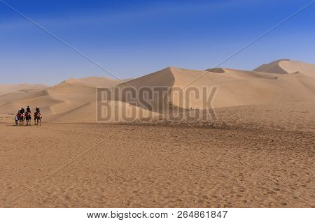 Dunhuang, China - August 8, 2012: Tourists Riding Cammels At The Echoing Sand Mountain Near The City