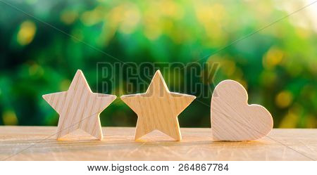 Two Stars And Heart On A Green Bokeh Background. Three Star Rating, The Choice Of The Editorial Offi