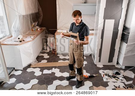 Focused Diligent Worker Inspecting Room And Planning Repairs Work. Repair Of The Dining Room In The